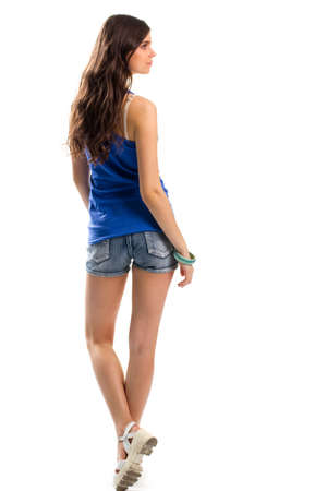 short shorts: Woman in blue tank top. Back view of short shorts. Casual outfit with sandals. Youth and lightness.
