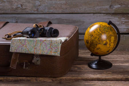 wherever: Binoculars and map on suitcase. Globe beside brown suitcase. Go wherever you want. Freedom is a treasure.