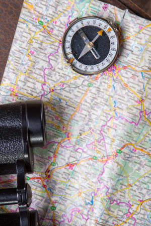 to move forward: Binoculars with compass on map. Black binoculars lying on map. Move forward with caution. Check the map if needed.
