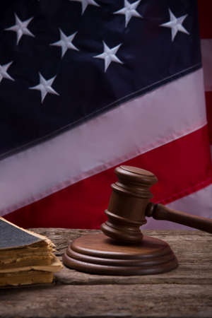 punish: Gavel on American flag background. Old book near gavel. Strong legal system. Find and punish those responsible.