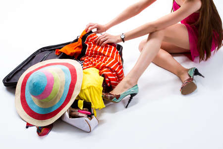 overfilled: Woman sitting near filled suitcase. Hands touch clothes on suitcase. I cant find summer dress. Lady packing things for trip.