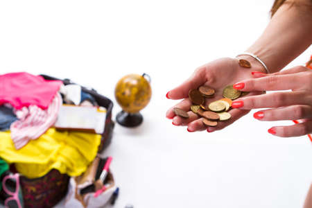 overfilled: Womans hand with coins. Filled suitcase in the background. Money that she can spend. Lets travel to another place.