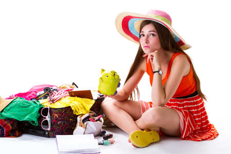 overfilled: Girl sits near filled suitcase. Young lady holds money box. Feeling sad before departure. This money isnt enough.