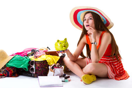overfilled: Girl sits beside overfilled suitcase. Lady with green money box. Best idea for vacation. Need some time to think.