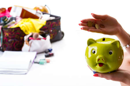 overfilled: Girls hand holding piggy bank. Coins and green money box. Time to count the savings. Lots of luggage for vacation. Stock Photo