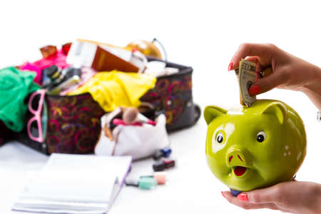 overfilled: Hand with a piggy bank. Womans hand holds dollars. Luggage and money for travelling. Save some money for later. Stock Photo