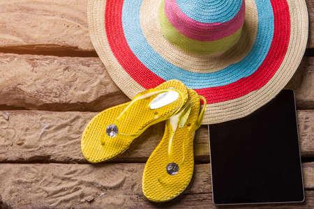 sandalias: Flips flops cerca de una tableta. Tablilla negra en la arena. Gadget de Lady con reproductor multimedia. Las vacaciones son para relajarse. Foto de archivo