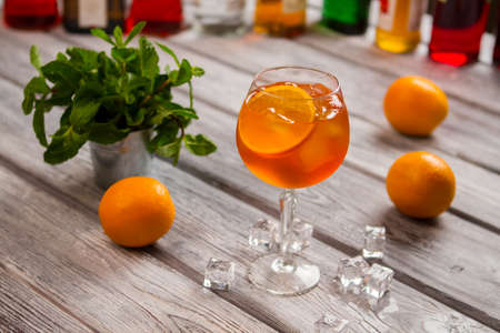 Wineglass with orange cocktail with Mint in small bucket. Stock Photo