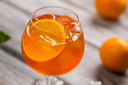 Orange drink in a wineglass with Ice and slice of orange.