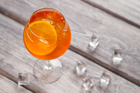 Orange cocktail in wineglass with Ice cubes on wooden background.