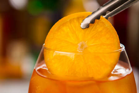 Tongs with slice of orange in Glass filled with drink. Stock Photo