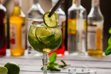 Tongs holding slice of lime. Beverage with leaves of mint. Stock Photo