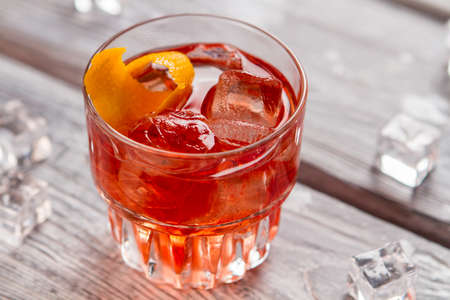sweet vermouth: Glass with dark orange drink. Lemon peel and ice cubes. Negroni cocktail is ready. Recipe of beverage with bitter.