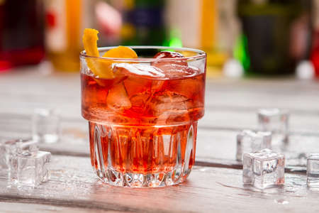 vermouth: Dark orange drink in glass. Ice cubes and lemon peel. Negroni served at local bar. Vermouth and gin. Stock Photo