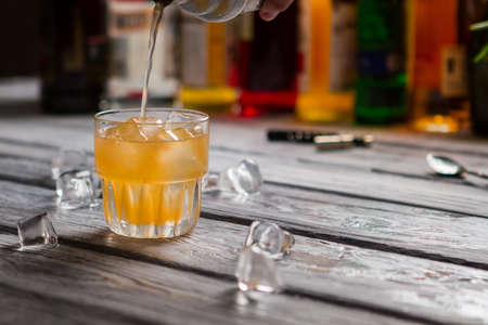 Orange liquid pours into glass and Melting ice on wooden surface. Stock Photo