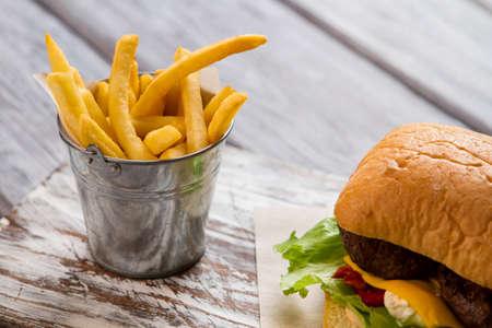 Secchio con patatine fritte e hamburger. Archivio Fotografico