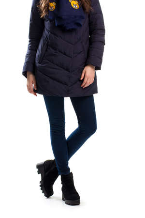 pants down: Woman in dark down jacket, Navy pants and black boots. Stock Photo
