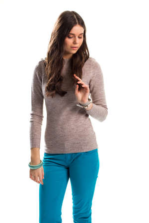 Young woman in beige sweater. Turquoise pants and bracelet. Beautiful casual clothes. Warm top for autumn.