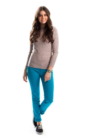 black sweater: Woman in beige sweater smiling, Turquoise pants and footwear.