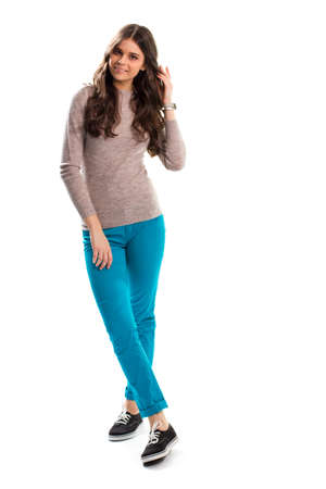 sudadera: Señora en la camiseta que toca el pelo, pantalones de color turquesa y suéter beige.