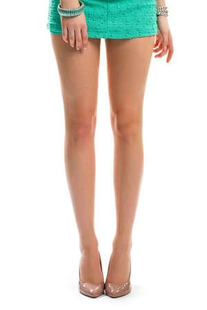 Piernas de la muchacha en zapatos de tacón de color beige.