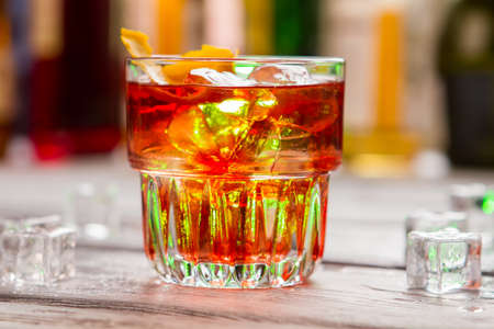 sweet vermouth: Glass with dark orange beverage. Ice and lemon rind.Sweet taste of Negroni. Dry gin of best quality.