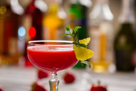 requires: Glass with bright red cocktail. Mint sprig on a glass. Beverage with lemon juice. Clover club recipe requires gin. Stock Photo
