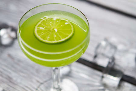 requires: Glass with green cocktail. Slice of lime. Daiquiri with sour juice. Recipe that requires fresh fruit. Stock Photo