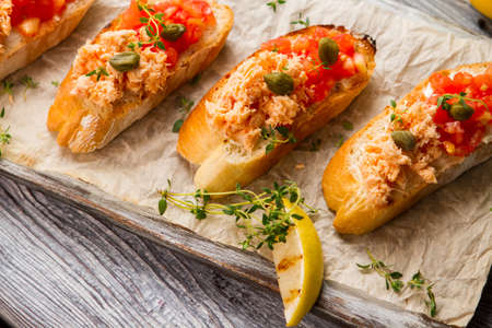 proven: Grilled lemon and toasts. Fish meat on baguette slices. Delicious food cooked at home. Proven recipe of salmon bruschetta. Stock Photo