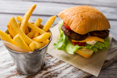 beefburger: Burger and bucket with fries. Fresh lettuce and bun. Typical fast food snack. Beefburger with cream cheese. Stock Photo