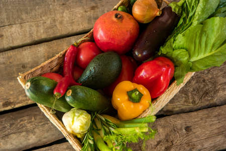 fruits in a basket: Chili peppers and pomegranate. Basket with wet vegetables. Different ingredients for salad. Food on old brown table.