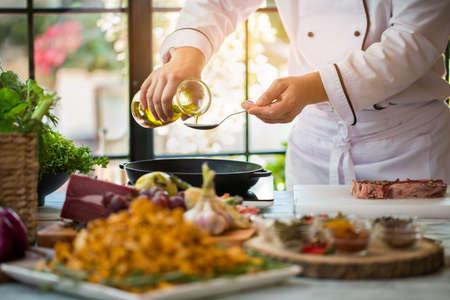 水差しは、スプーンに液体を注ぐ。スパイスと生の肉。高品質オリーブ オイル。レシピに必要な脂肪を植えます。 写真素材