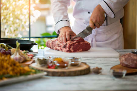 Hand with knife cuts meat. Cooking board on gray table. Beef tenderloin for steak. Chef is working in restaurant.