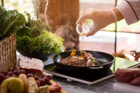 Fles giet vloeistof op de pan. Vlees en groene groente. Gebakken rundvlees en asperges. Chef maakt flambe steak.