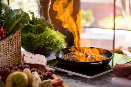 pan: Flames in frying pan. Piece of meat being fried. Proven recipe of flambe steak. Asparagus wrapped in bacon strips.