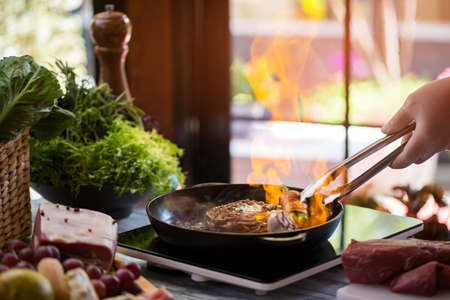 Tongs berühren Fleisch auf Pfanne. Lebensmittel gebraten werden. Wie flambierte Steak zu machen. Teuer Gericht in neuen Restaurant.