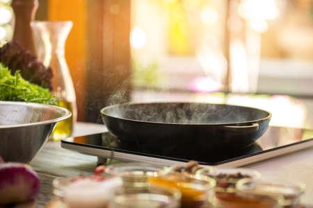 프라이팬에서 스팀. 검은 휴대용 밥솥. 맛있는 음식을 조리하려면 숙달이 필요합니다. 저녁은 어때? 스톡 콘텐츠
