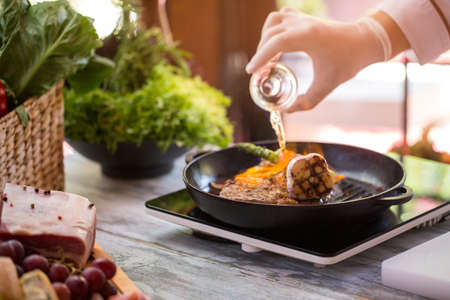 Bottle pours liquid on pan. Meat is burning. How to cook steak fast. Special recipe from chef. Stock Photo
