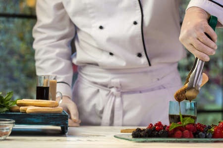 mastery: Hand with tongs holding biscuit. Glass with dark liquid. Chef dips savoiardi into coffee. Mastery of confectioner. Stock Photo