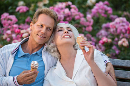 priceless: Man smiles and hugs woman. Couple with ice cream. Lets have a rest together. Every moment is priceless.