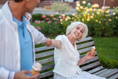 dont walk: Man pulls mature womans hand. Smiling lady with ice cream. Dont be so lazy. Lets go for a walk.