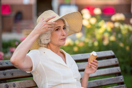 coolness: Mature woman with ice cream. Lady touches her hat. Serious thoughts come to mind. Coolness of the shade.