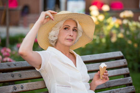 ice cream woman: Mature lady with ice cream. Woman touching her hat. Spending summer in home city. Look to the side.