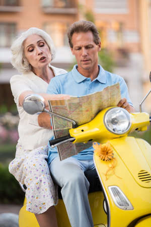 Mature people sitting on scooter. Man with map beside woman. We should turn here. I dont know this town.