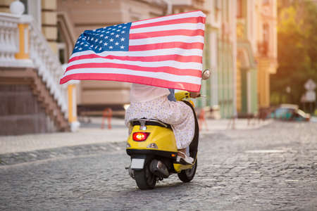 old flag: Couple is riding a scooter. Flag of US. Travelling around America. Free as a bird.