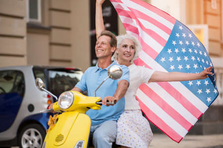 old flag: Mature couple riding yellow scooter. Woman raises USA flag. Love and pride. Warm hearts and bright smiles.