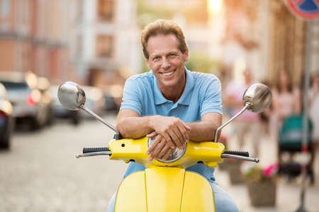 actively: Mature guy is smiling. Man sits on yellow scooter. Spend your free time actively. Tourist in the city. Stock Photo