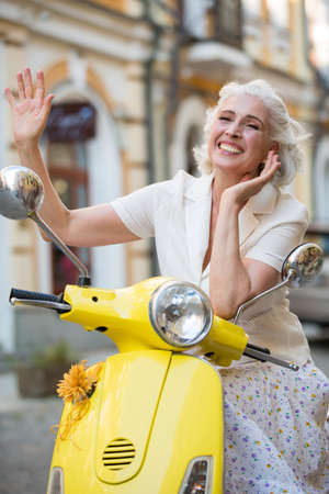 with ease: Mature lady waves hand. Lady on scooter is smiling. Meet old friends on vacation. Feeling at ease.