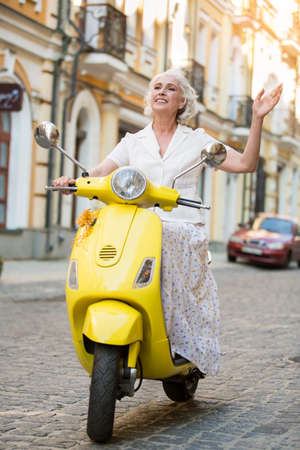 Lady on scooter waves hand. Mature woman is kindly smiling. Vacation and happiness. Say goodbye to problems.