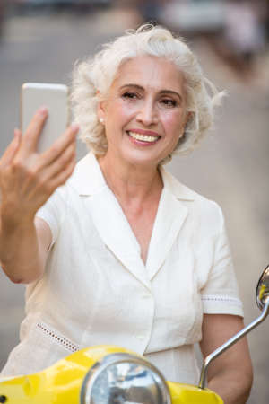 capture the moment: Smiling lady looks at phone. Mature woman with happy face. How do i look. Selfies during vacation.